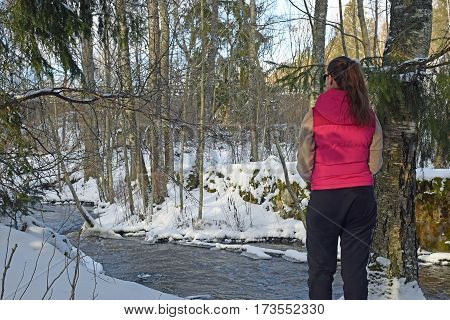 Young woman standing in wintry forest and watching a creek. Horizontal image.