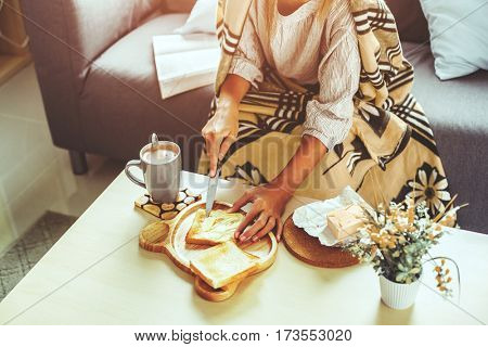 Unrecognizable girl wrapped in blanket relaxing with cocoa and breakfast on a couch in living room. Comfortable weekend morning.