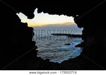 View onto the ocean during sunset through one of the windows at the Ana Kakenga Cave or two windows cave in Easter Island Rapa Nui Chile South America