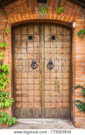 antique wrought iron door with knocker ivy grows around doors