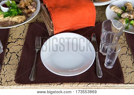 on the brown napkin on the table is flatware per person fork knife two glasses on the background there are rolls of eggplant and grilled vegetables