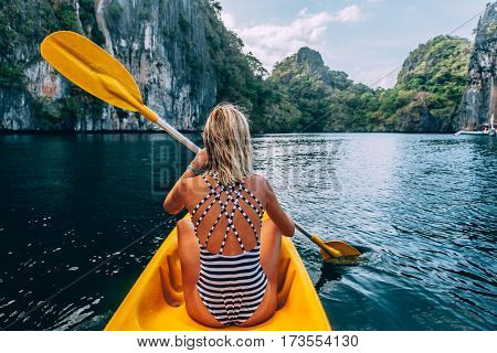 Woman paddling a kayak in the island lagoon between mountains. Kayaking in El Nido, Palawan, Philippines.