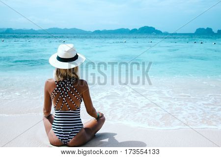 Back view of the young woman in bikini and hat relaxing on the tropical beach and looking at the sea view with islands