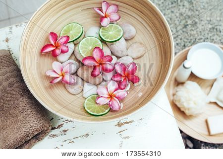 Foot bath in bowl with lime and tropical flowers, organic spa pedicure treatment
