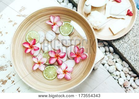Foot bath in bowl with lime and tropical flowers, organic spa pedicure treatment, top view.
