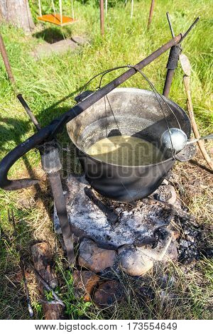 a pot of soup on the coals. a pot of soup on the coals. near the pot there are a scoop and spoon
