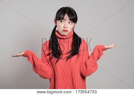Studio portrait of 20 year old female Asian woman with both hands in absurd situation