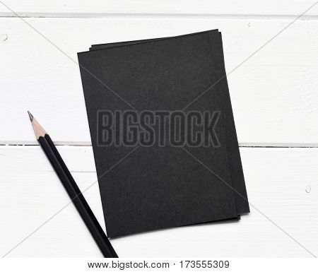 sheets of black paper with pencil on a white table