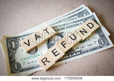 Wooden block word VAT REFUND and Dollar banknote on wooden background