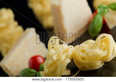 Pasta Tagliatelle, Parmesan Arranged On Marble Table.  Delicious Dry Uncooked Ingredients For Tradit