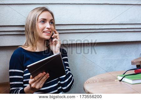 Happy female sitting in cafe and talking on mobile phone during work on touch pad, young girl is surprised by what he saw tablet in hand having conversation on smartphone