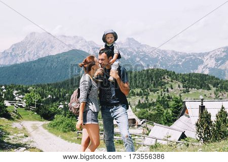 Beautiful happy family spends time on nature in the mountains. Family background. Lifestyle Travel concept. Parent and child together. Velika Planina or Big Pasture Plateau in the Kamnik Alps Slovenia