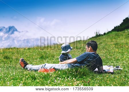 Father with son spends time on nature in the mountains. Family background. Lifestyle Travel concept. Parent and child together. Velika Planina or Big Pasture Plateau in the Kamnik Alps Slovenia.