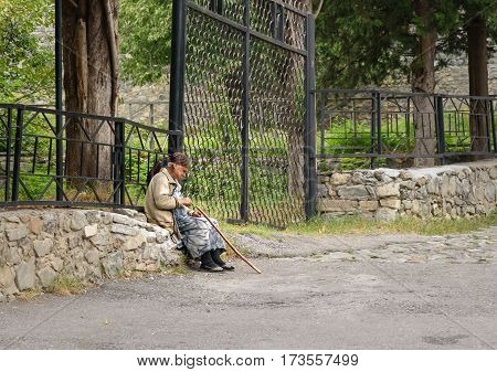 Sheki Azerbaijan - September 13 2016: Unidentified Azerbaijani elderly woman sitting on rocks in Sheki fortress
