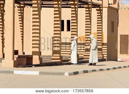 Merzouga Morocco - Jan 6 2017: Two Moroccan men in white djellaba talk on the street in Merzouga village