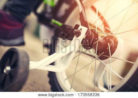 Close up of children's new bicycle with extra caster