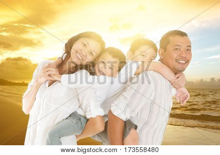 Asian family relaxed at beachside in the beautiful sunset