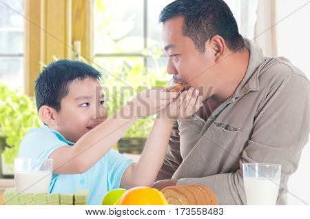Lovely asian child feeding father with cake