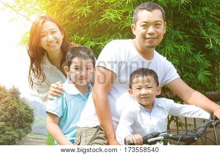 Asian family enjoy cycling in the beautiful sunset