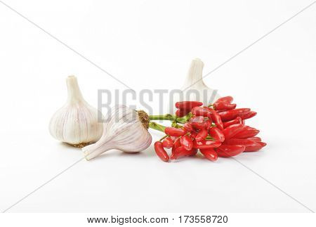 Bunch of small red chili peppers and garlic bulbs on white background