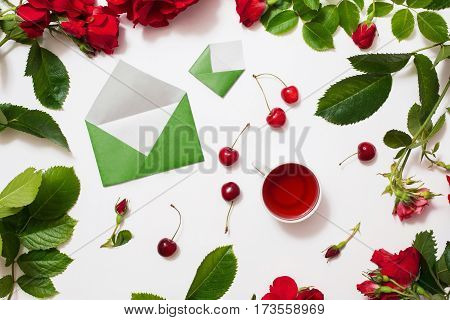 Red tea ripe cherries small envelopes with green leaves roses lay on white background. Tea drinking during work. Healing drink. Aromatic morning. Berry compote. Flat lay top view. Flower frame