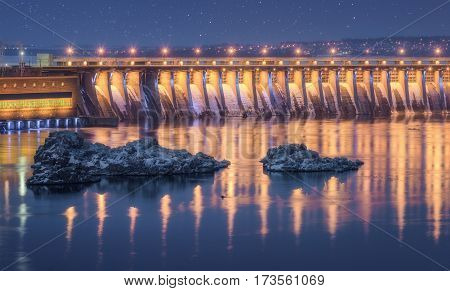 Dam. Beautiful night industrial landscape with dam hydroelectric power station bridge river city illumination reflected in water rocks and blue starry sky in winter in Ukraine. Cityscape