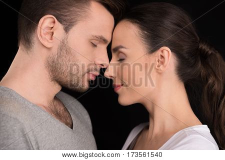 side view of couple in love bonding to each other on black