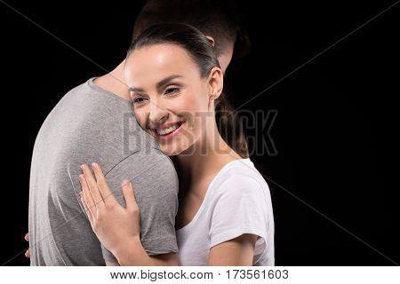 portrait of smiling woman bonding to man and looking away on black