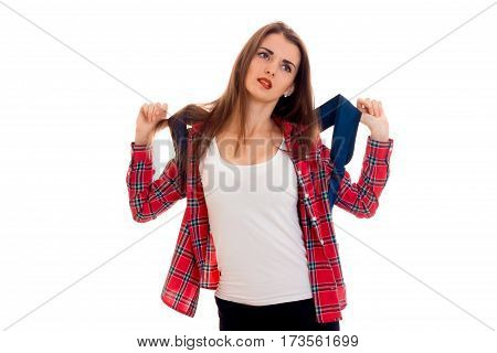 young girl in t-shirt and Plaid Shirt keeps a heavy Briefcase on his shoulders and looks up isolated on white background