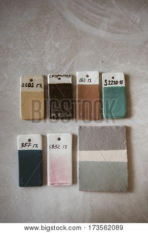 Top view on colored glazed ceramic samples on grey table in workroom