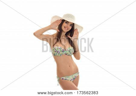 beautiful young girl in a bathing suit with hat on your head looks into the camera and smiling isolated on white background