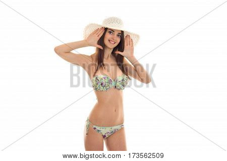 beautiful young girl with an attractive body in a bathing suit and hat looks into the camera and smiling isolated on white background