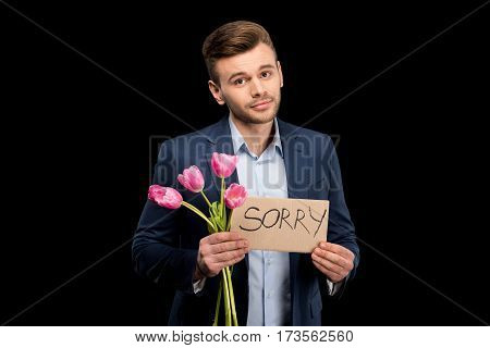 Handsome young man with pink tulips and sorry sign hopefully looking at camera