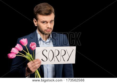 Ashamed young man with tulips and sorry sign looking at camera