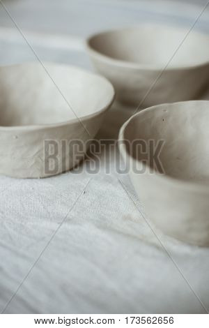 Grey raw ceramic ware on table with industrial fabric