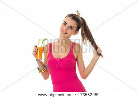 attractive young girl in a bright t-shirt holding a glass of juice with one hand and the second hand keeps hair and smiling isolated on white background.