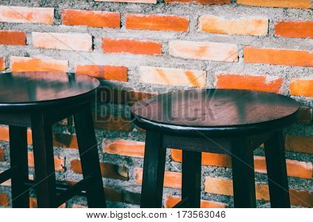 wooden chairs in bar against red brick wall