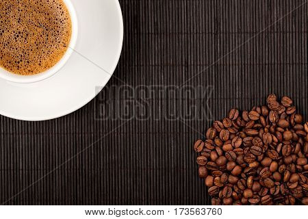 White coffee cup and crops on bamboo coaster. Place for text.