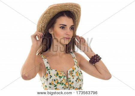 cute young girl in the summer and looks toward Sarafan keeps hand on Hat isolated on white background