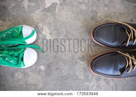 Father's business shoes and kids sneakers on a cement floor concept of family