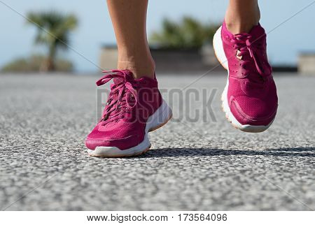 Runner woman feet running on road training for fitness and healthy lifestyle