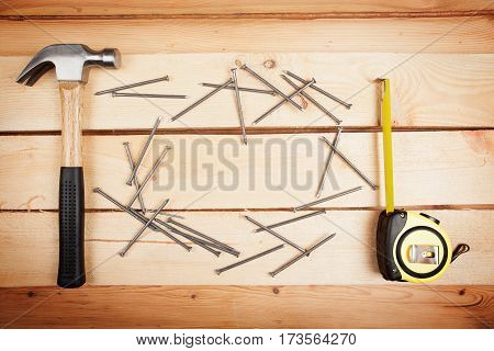 Wood background with a hammer ruler and some nails home improvement concept