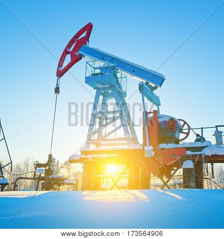 Oil field. Oil pump. The oil pumping unit against the background of morning dawn in the winter.