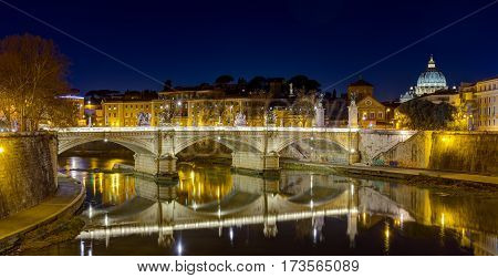 Ponte Vittorio Emanuele II and Tiber river by night, St. Peter basilica in the background, Rome, Italy.