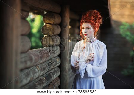 Beautiful redhead girl princess with a high hair in an old white dress in the park. The Victorian era. Historic costume. White Queen. Princess castle. Redhead princess