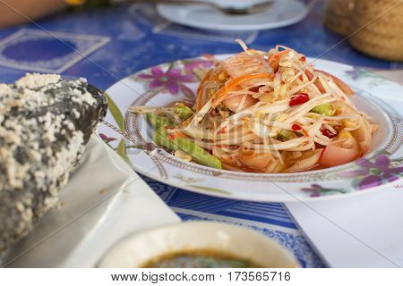 Papaya salad in bowl on table with selective focus.