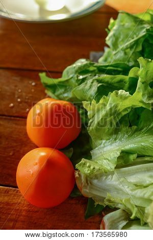 Red tomatoes and green lettuce on a wooden table. Useful vegetables. Healthy lifestyle. Selective focus.