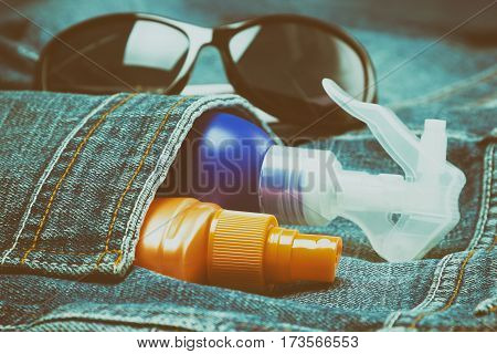 Sunscreen cosmetic products in jeans pocket with sunglasses. Skin care cosmetics containing sun protection factor. Shallow depth of field