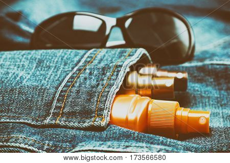 Sunscreen cosmetic products in jeans pocket with sunglasses. Skin care cosmetics for safe tan. Shallow depth of field