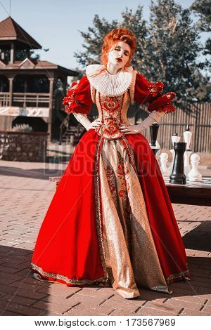 Red Queen in the castle. Red-haired woman in a chic vintage dress. Fashion Photo